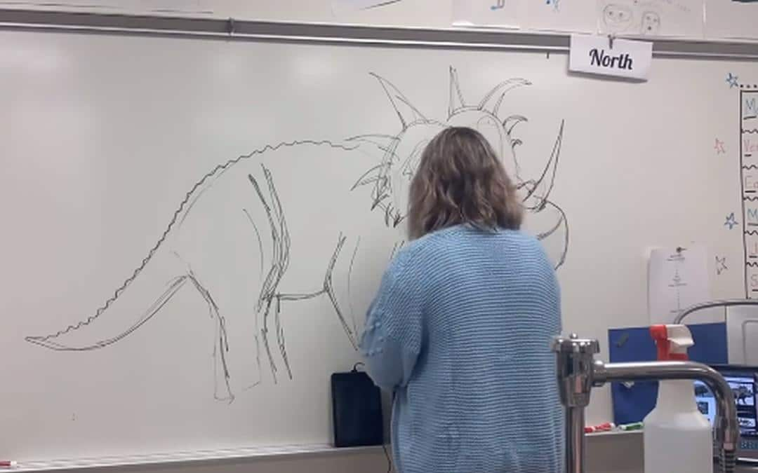 Lerares tekent elke dag een dinosaurus op het bord