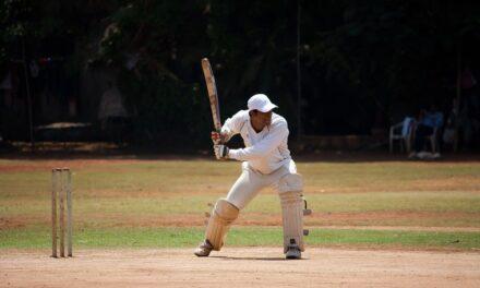 Cricketspeler slaat bal het speelveld uit, door het voorraam van zijn auto