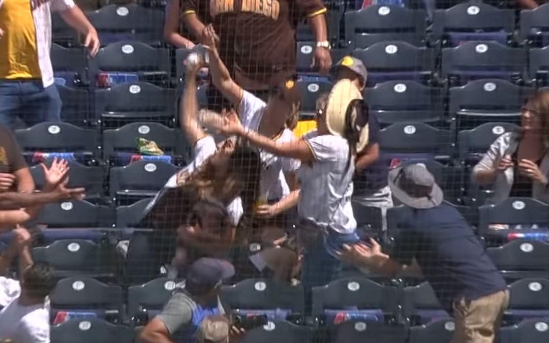Moeder met baby op arm vangt honkbal